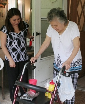woman helping a older female with a walker